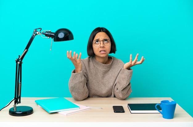 Молодой студент смешанной расы женщина учится на столе подчеркнул подавлен
