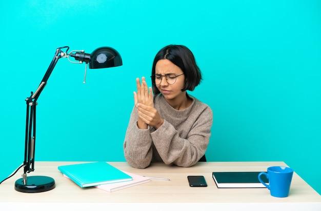 손에 통증을 앓고 테이블에서 공부하는 젊은 학생 혼혈 여자