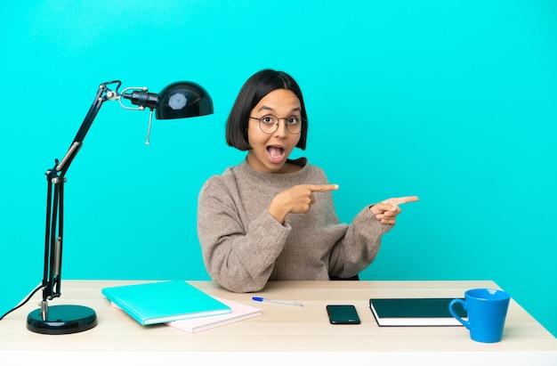 Молодой студент смешанной расы женщина учится на столе удивлен и указывая сторону