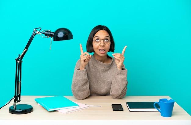 Молодой студент смешанной расы женщина учится на столе удивлен и указывая вверх