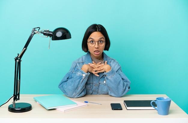 Молодой студент смешанной расы женщина учится на столе удивлен и шокирован, глядя вправо