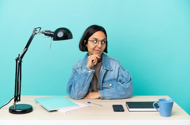 見上げながらアイデアを考えてテーブルで勉強している若い学生混血の女性
