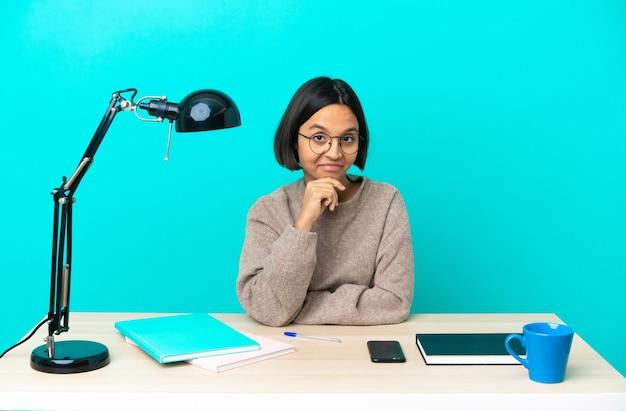 Молодой студент смешанной расы женщина учится на мышлении стола