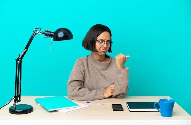 Молодой студент смешанной расы женщина учится на столе недовольна и указывая в сторону