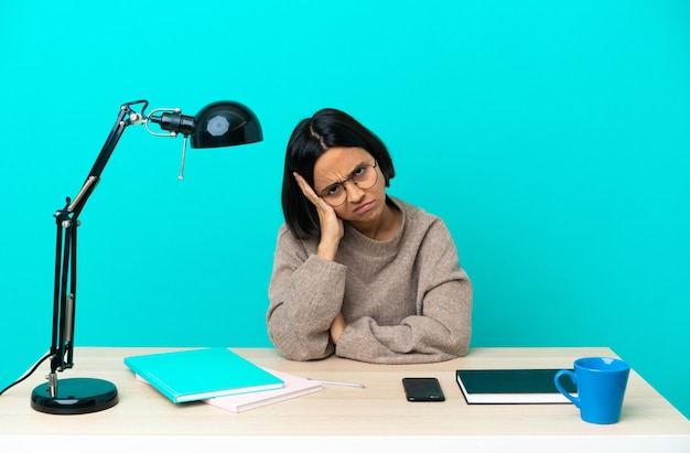 좌절의 표정으로 테이블에 공부하고 이해하지 못하는 젊은 학생 혼혈 여자