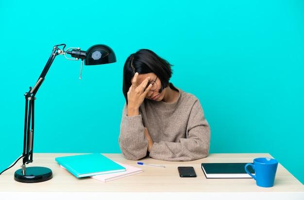 頭痛のあるテーブルで勉強している若い学生混血の女性 Premium写真
