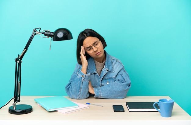 두통 테이블에 공부하는 젊은 학생 혼혈 여자