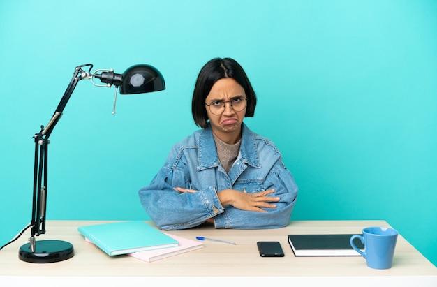 Молодой студент смешанной расы женщина учится на столе с грустным выражением лица
