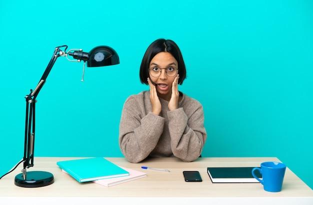Молодая студентка смешанной расы учится на столе с удивленным и шокированным выражением лица