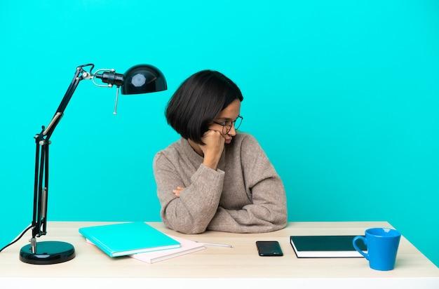 Молодая студентка смешанной расы учится на столе с усталым и скучающим выражением лица