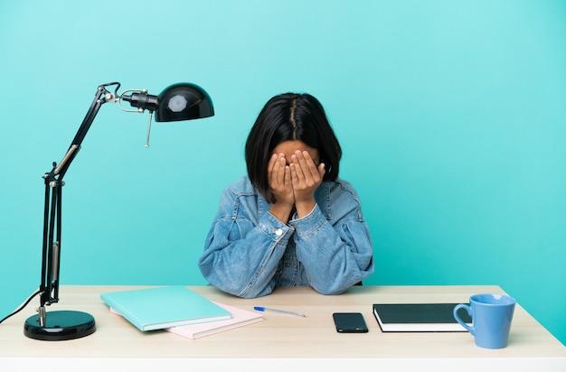 Молодой студент смешанной расы женщина учится на столе с усталым и больным выражением лица