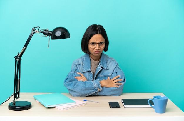 Молодой студент смешанной расы женщина учится на столе с несчастным выражением лица