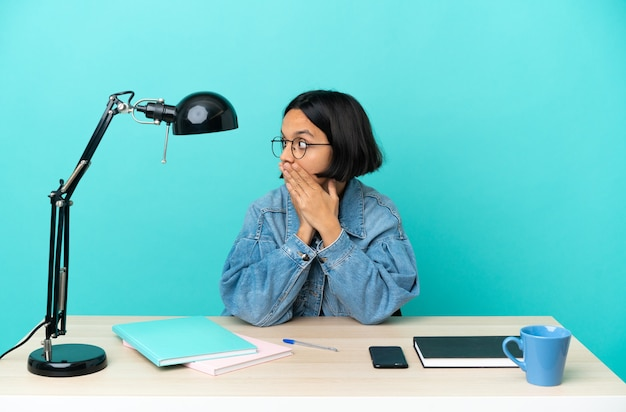 Young student mixed race woman studying on a table covering mouth and looking to the side