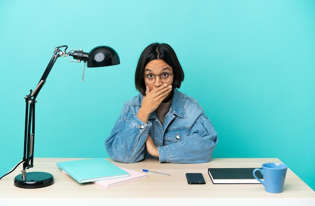 Young student mixed race woman studying on a table covering mouth with hand