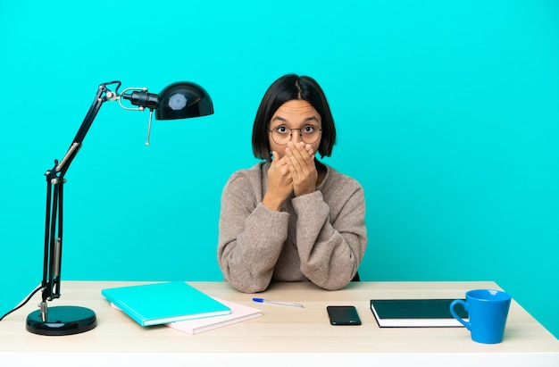Young student mixed race woman studying on a table covering mouth with hands
