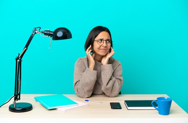 Young student mixed race woman studying on a table frustrated and covering ears