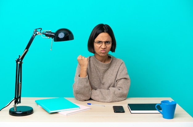 Young student mixed race woman studying a table with unhappy expression