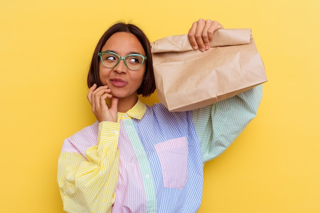Young student mixed race woman taking lunch isolated on yellow wall