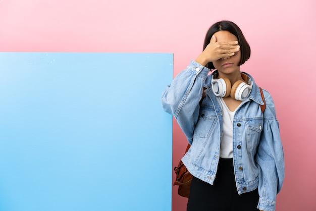 若い学生の混血の女性は、大きなバナーの孤立した背景を手で覆っています。何かを見たくない