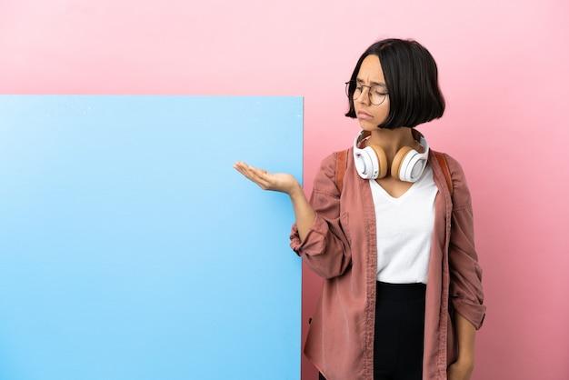 Молодой студент смешанной расы женщина с большим баннером изолировал фон, держа copyspace с сомнениями
