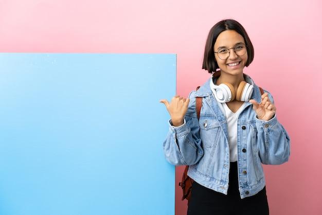 Молодая студентка смешанной расы с большим баннером изолировала фон, указывая в сторону, чтобы представить продукт