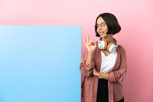 Молодая студентка смешанной расы с большим знаменем изолировала фон, показывая пальцами знак ок