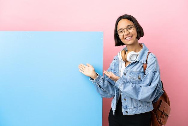 Молодая студентка смешанной расы с большим знаменем на изолированном фоне, протягивающая руки в сторону для приглашения приехать