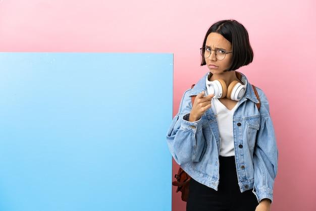 Молодая студентка смешанной расы с большим знаменем на изолированном фоне разочарована и указывает вперед