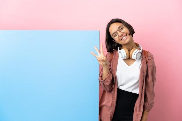 幸せで、指で3を数える孤立した背景の上の大きなバナーを持つ若い学生混血の女性
