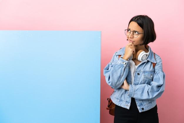 Молодой студент смешанной расы женщина с большим знаменем на изолированном фоне, сомневаясь