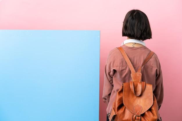 Молодой студент смешанной расы женщина с большим знаменем на изолированном фоне в задней позиции и глядя сторону