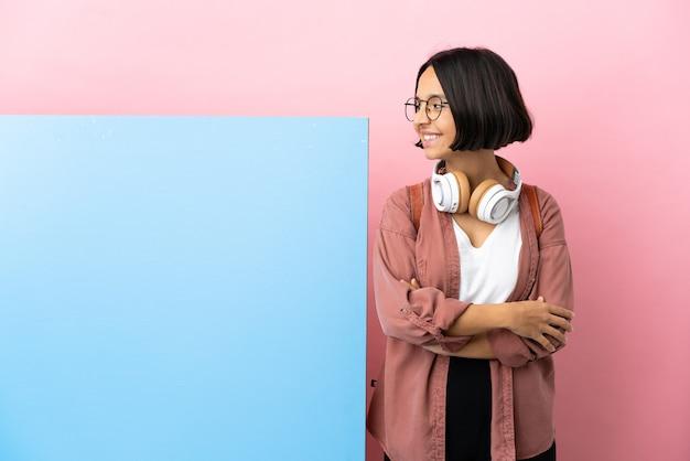 Молодой студент смешанной расы женщина с большим знаменем на изолированном фоне смотрит в сторону и улыбается