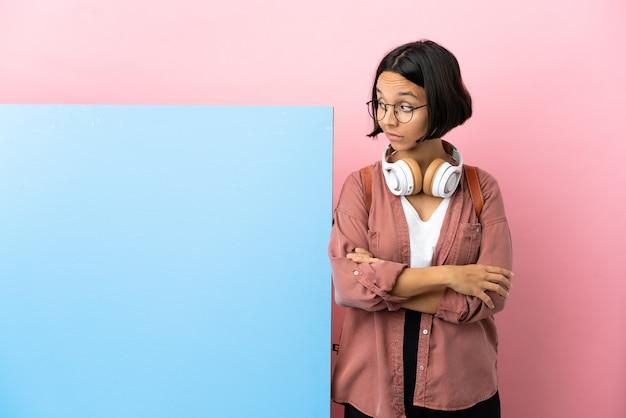 Молодой студент смешанной расы женщина с большим знаменем на изолированном фоне, делая жест сомнения глядя сторону