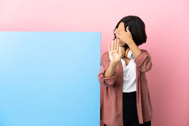 Молодая студентка смешанной расы с большим знаменем на изолированном фоне делает стоп-жест и закрывает лицо