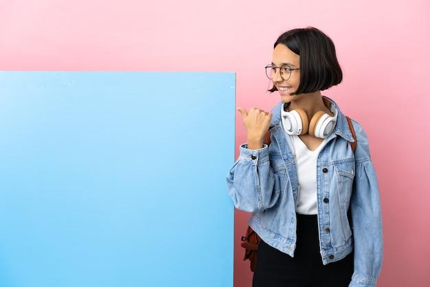 Молодой студент смешанной расы женщина с большим баннером на изолированном фоне, указывая в сторону, чтобы представить продукт
