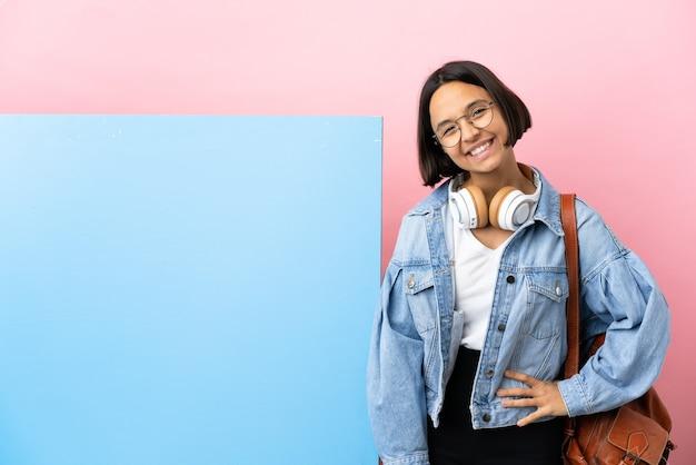 Молодая студентка смешанной расы с большим знаменем на изолированном фоне позирует с руками на бедрах и улыбается
