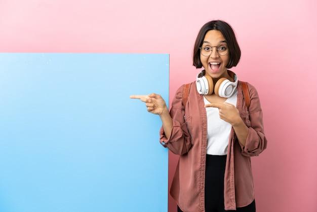 Молодая студентка смешанной расы с большим знаменем на изолированном фоне удивлена и указывает сторону