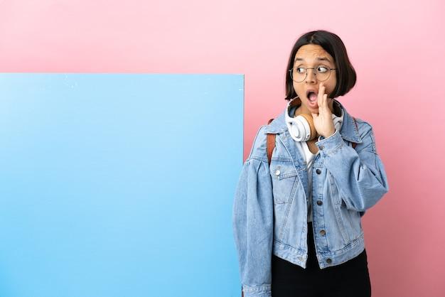 Молодая студентка смешанной расы с большим знаменем на изолированном фоне шепчет что-то с удивленным жестом, глядя в сторону