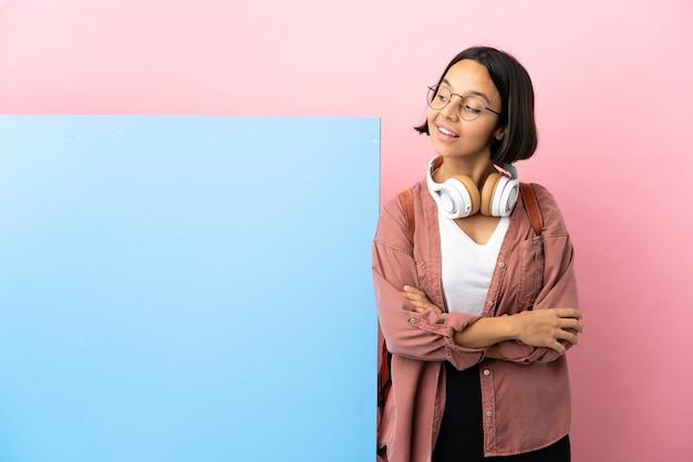 Молодой студент смешанной расы женщина с большим знаменем на изолированном фоне со скрещенными руками и счастливыми