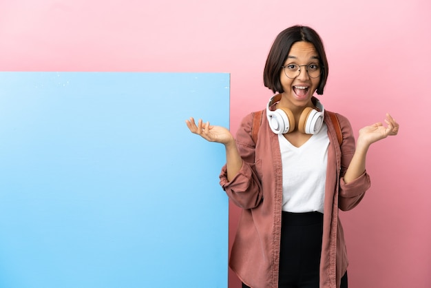 ショックを受けた顔の表情と孤立した背景の上の大きなバナーを持つ若い学生混血の女性