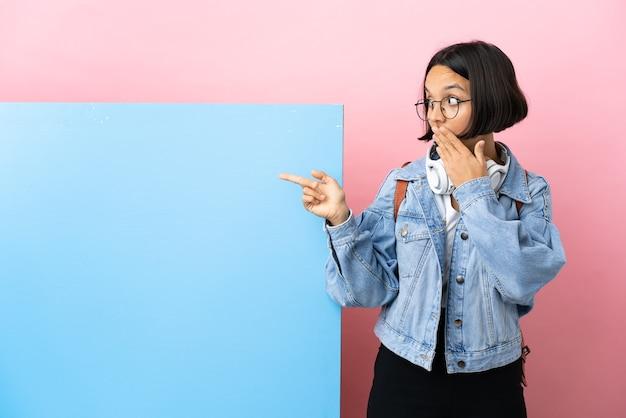 Молодая студентка смешанной расы с большим знаменем на изолированном фоне с удивленным выражением лица, указывая сторону