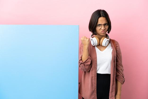 Молодой студент смешанной расы женщина с большим баннером над изолированной стеной с несчастным выражением лица