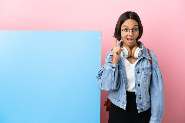 Young student mixed race woman with a big banner over isolated background intending to realizes the solution while lifting a finger up