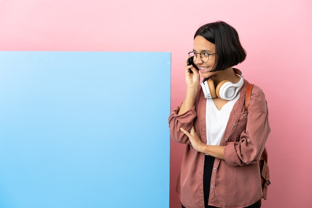 Young student mixed race woman with a big banner isolated background keeping a conversation with the mobile phone with someone
