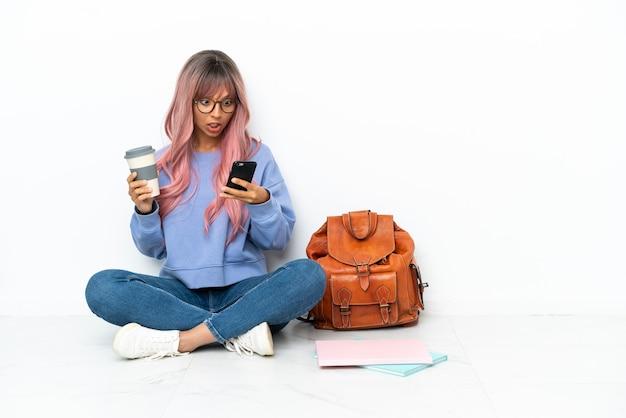 Молодой студент смешанной расы женщина с розовыми волосами сидит на полу на белом фоне, держа кофе на вынос и мобильный