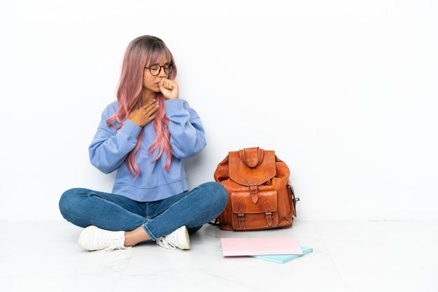 흰색 배경에 격리된 바닥에 앉아 있는 분홍색 머리를 한 젊은 혼혈 여성은 기침을 하고 기분이 나쁩니다