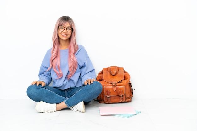 Молодой студент смешанной расы женщина с розовыми волосами сидит на полу на белом фоне смеясь