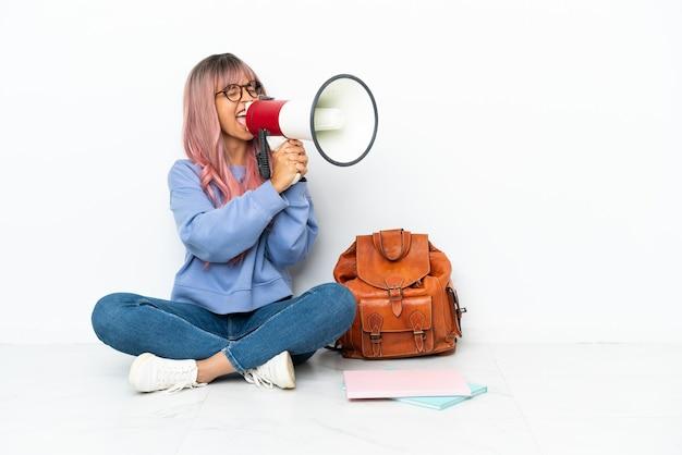 Молодая студентка смешанной расы с розовыми волосами сидит на полу на белом фоне и кричит в мегафон