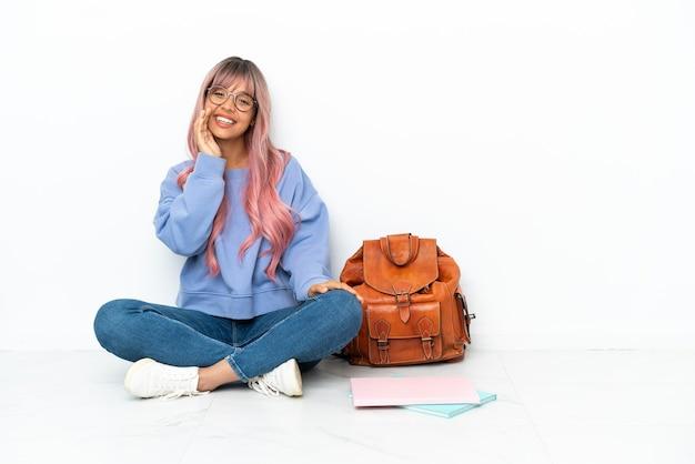 口を大きく開いて叫んで白い背景で隔離の1つの床に座っているピンクの髪の若い学生混血の女性