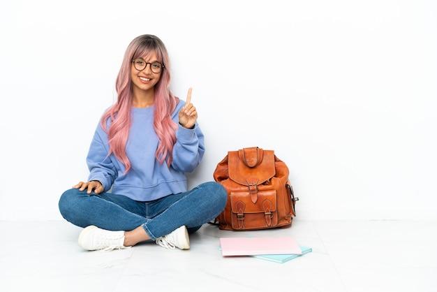 Молодая студентка смешанной расы с розовыми волосами сидит на полу на белом фоне, показывая и поднимая палец